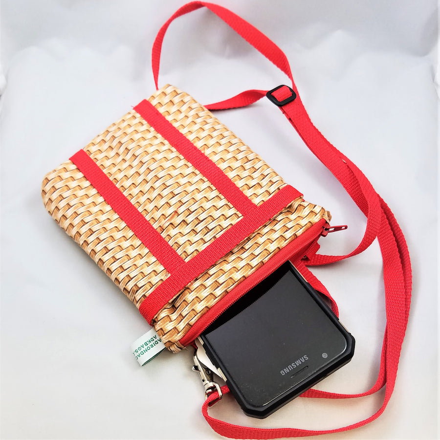 red strap bag flat with cell phone popping out