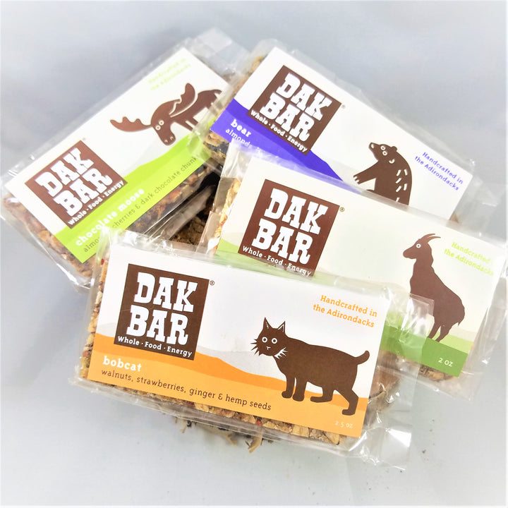 Pile of Dak bars . Visible are the Moose on the Chocolate Moose, the Bear on the almond, wild blueberries & maple; the Goat on the Green Goat, green apple, maple & walnut; and the Bobcat on the walnuts, strawberries and seeds
