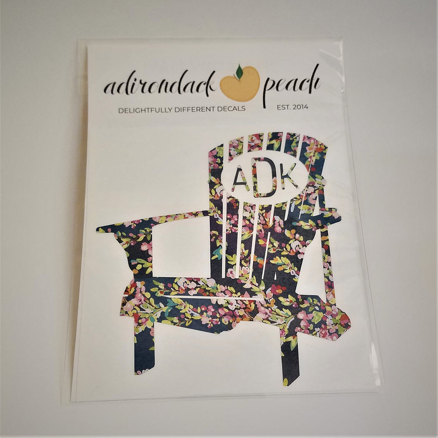 Decal of Adirondack chair in floral pattern with white oval and matching flora lettering ADK on chair back.