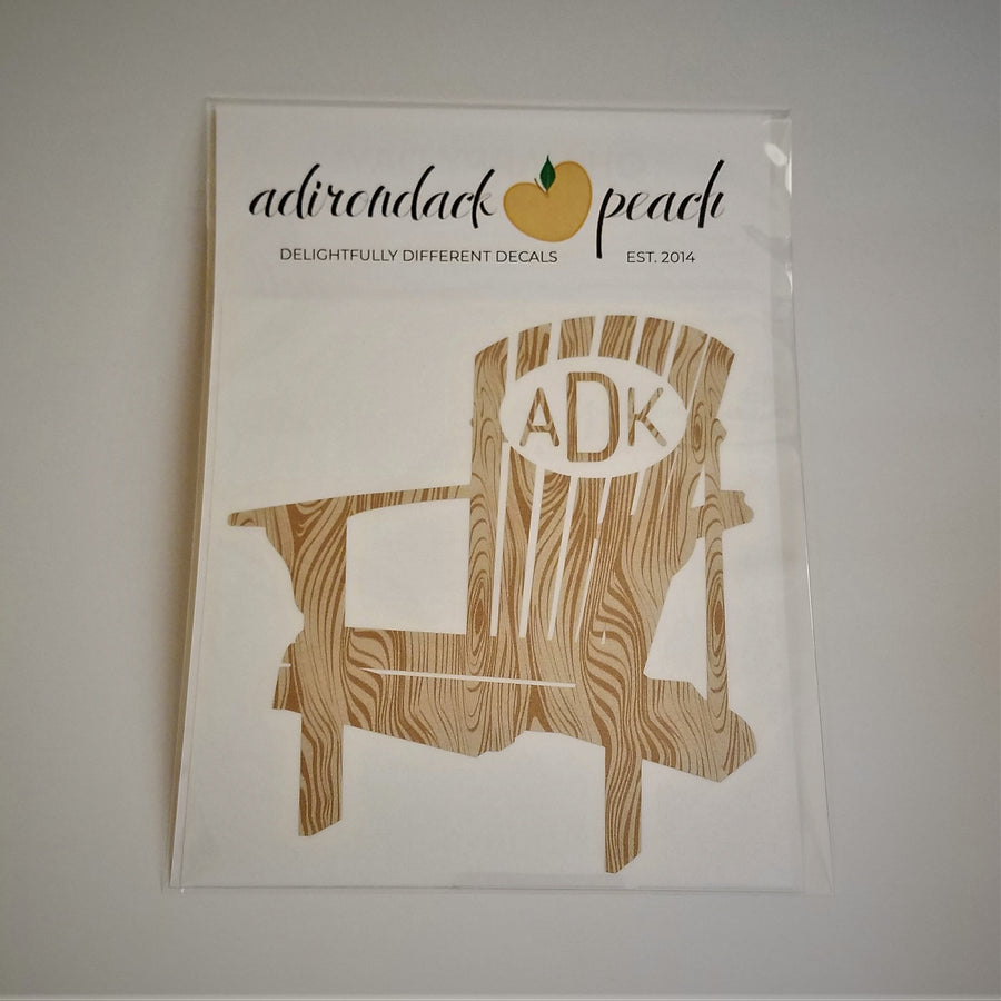 Decal of Adirondack chair in wood grain pattern with white oval and matching wood grain lettering ADK on chair back.