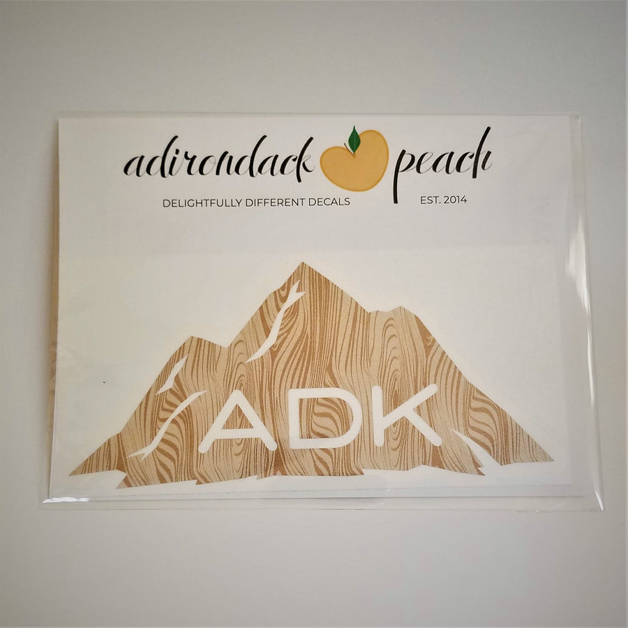 Adirondack mountain decal in wood grain pattern with white ADK lettering printed at the base of the mountain