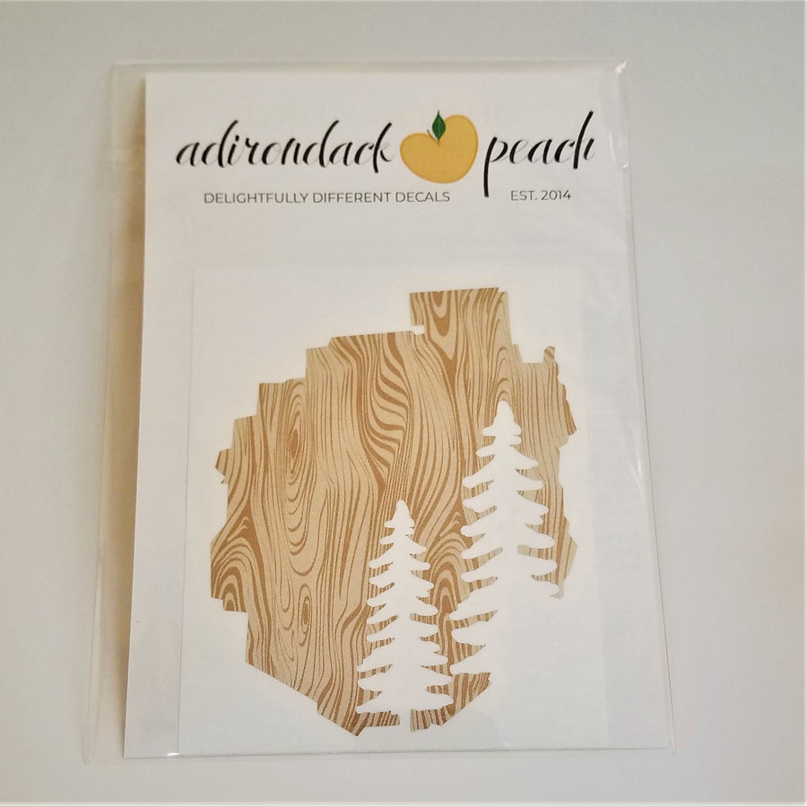 Decal of the Adirondack Park boundaries in wood grain pattern with two pine trees in white on the bottom right.