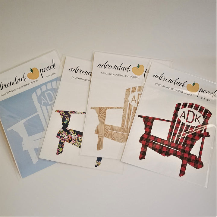Fanned out display of Adirondack chair decals in white, floral,  wood grain, and buffalo plaid with an oval in top of chair with ADK lettering showing on some of the chair decals.
