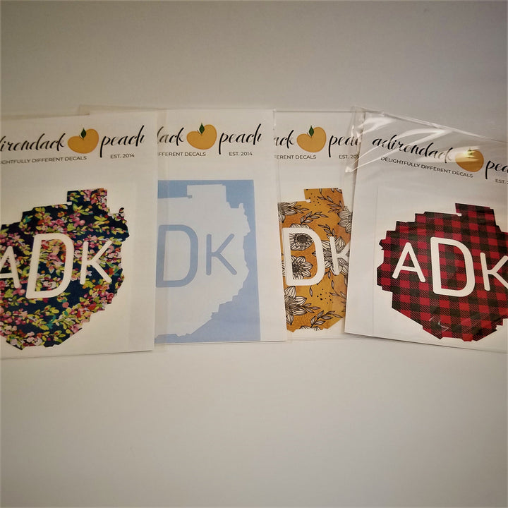 Fanned out display of Adirondack Park boundaries decals in navy floral pattern, white, yellow floral and buffalo plaid pattern with white ADK lettering printed in the middle of the decals