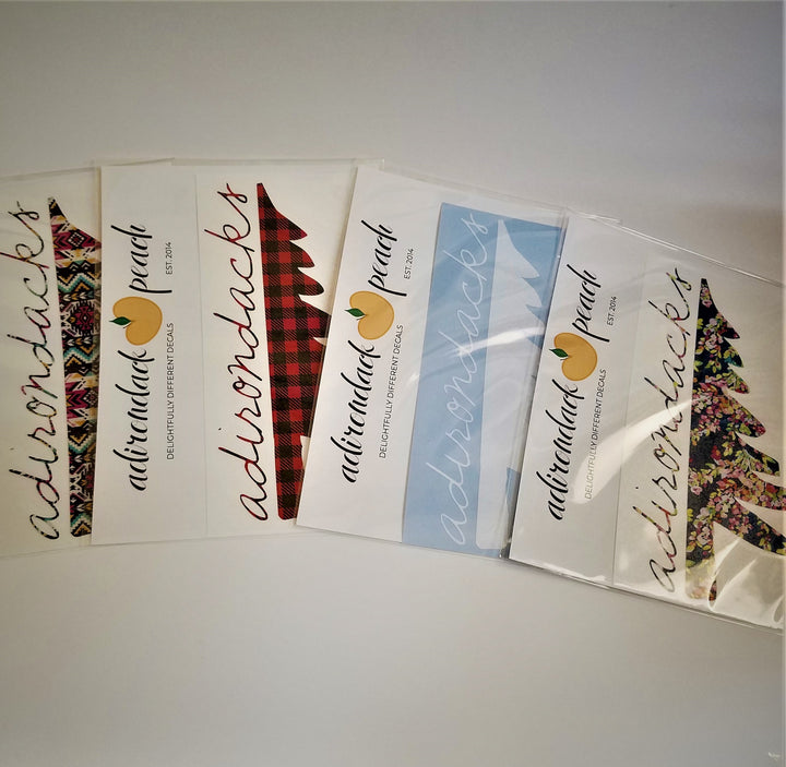 Fanned out display of Adirondack Peach half pine tree decals. Four packets display the pink aztec, buffalo plaid, white and navy floral patterns.