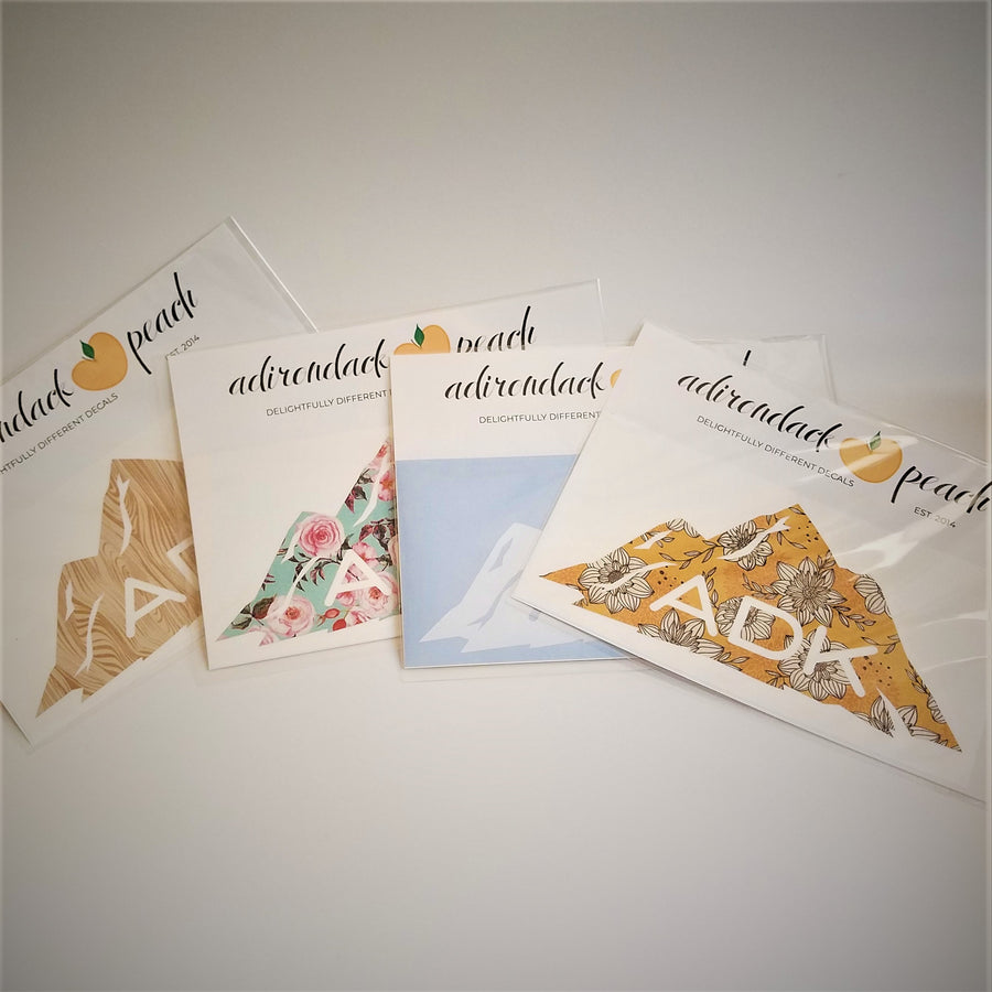 Fanned out display of Adirondack mountains decals in wood grain pattern, aqua floral, white,  and yellow floral with white ADK lettering printed at the base of the mountain range seen on some and peaking through.