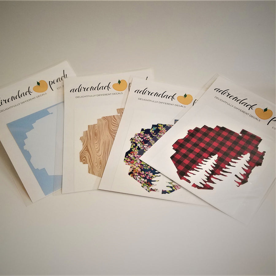 Fanned out display of Adirondack Park boundaries decals in white, wood grain, navy floral and buffalo plaid pattern with two white pine trees seen in full on the buffalo plaid pattern.