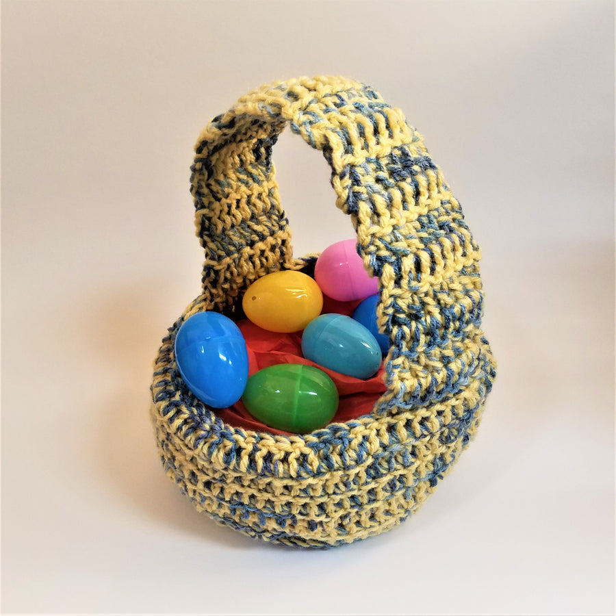 Crocheted Easter Basket n blue and yellow hues with assorted colored plastic eggs in the basket.