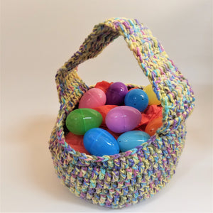 Crocheted Easter Basket in pastel colors--pale pinks, yellows, blues, purple --filled with assorted colors of plastic eggs.