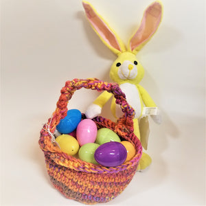 Crocheted Easter Basket in multi-colored yarns of pin, purple and yellow. Yellow and white bunny standing behind the basket.