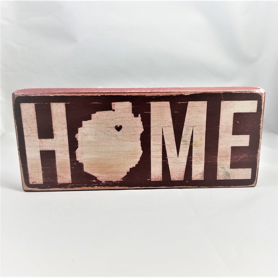 Red wood sign standing upright with white letter. The O in HOME is the shape of the Adirondack Park with a heart in the upper right side