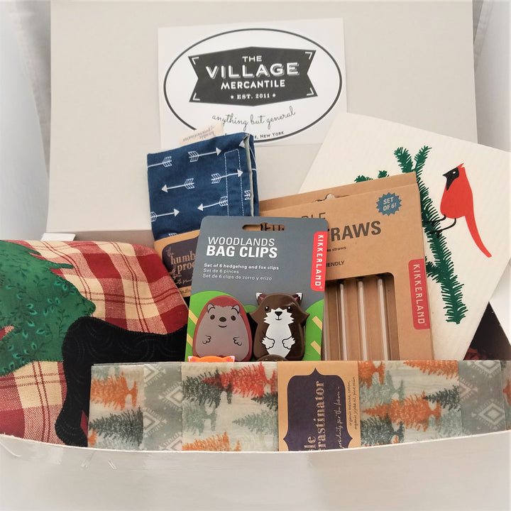 Close up on the items in the Kitchen box. Lower front wax wrap, behind that Woodland bag clips stand in front of a box of glass straws with a Swedish dishtowel sticking out in the back. On the left side is an Adirondack red plaid tea towel and a navy blue reusable cloth snack pouch.
