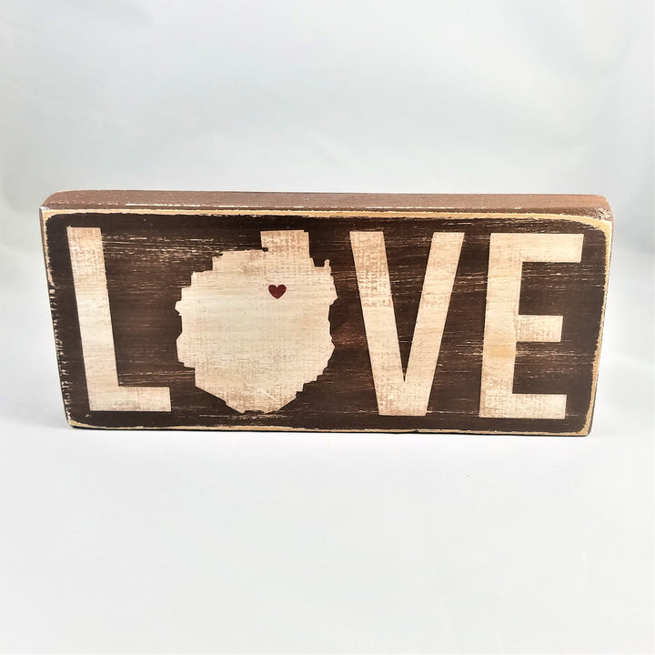Brown sign standing upright with white lettering. The O in the word love is in the shape of the Adirondack Park with a heart in the upper right side