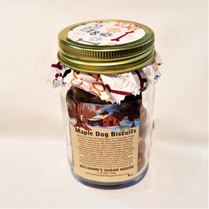 Mason jar packing with Maple Dog Biscuit beige label, fabric-lined top of jar with white fabric colored with brown and gray bones, yellow and gray paw prints, and decorative lettering like ruff.
