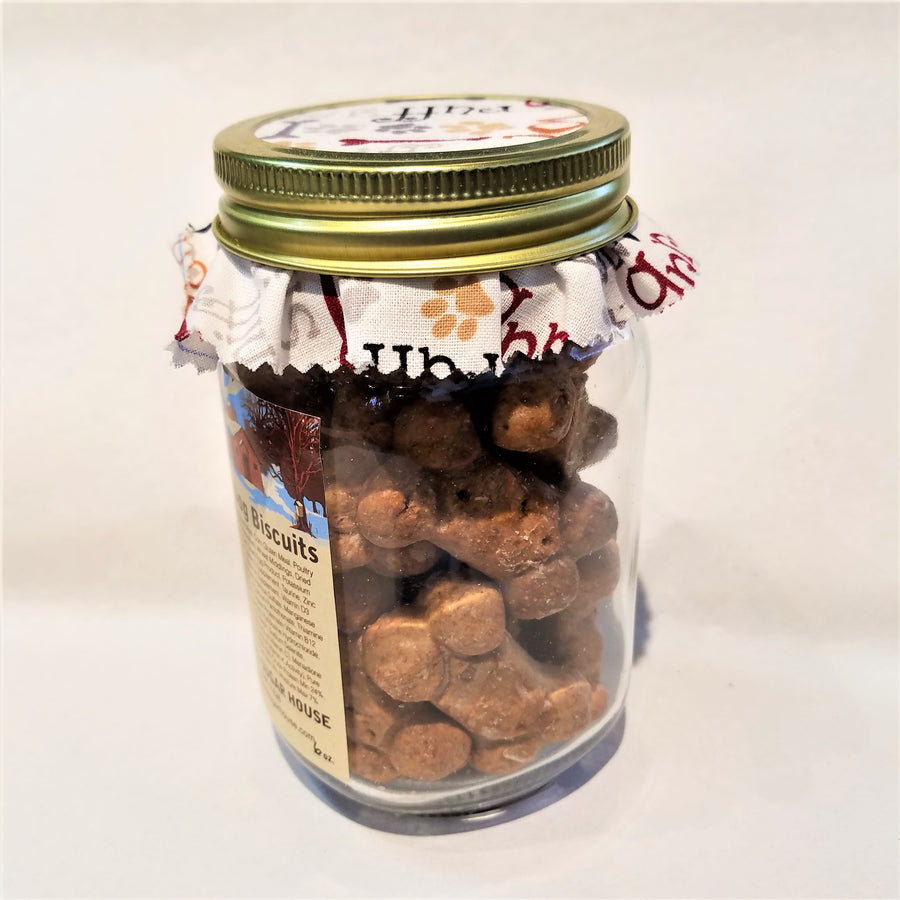 Side, standing view of  the clear part of the mason jar showing the maple dog biscuits inside with the fabric-lined top of jar also visible.