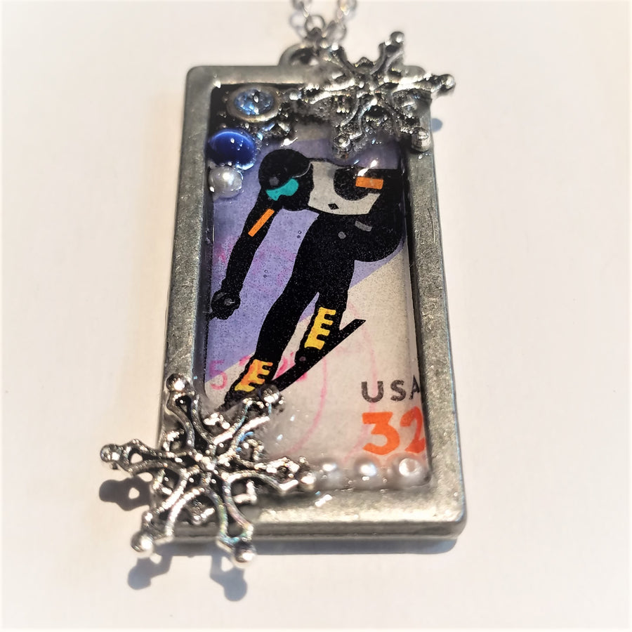 Silver-framed pendant with skier stamp in side. Silver snowflake and white beads on bottom; white bead and blue glass bead on top with another snowflake, a very small piece of silver chain showing at the top.
