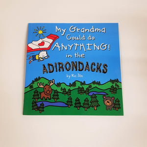 Cover of the square book, My Grandma Could Do Anything in the Adirondacks with type displayed in white lettering and wood-style font for Adirondacks. The cover drawing includes a bright blue sky with small yellow sun and a person attached to a hang glider soaring over green mountains, evergreens , a moose and a bear.