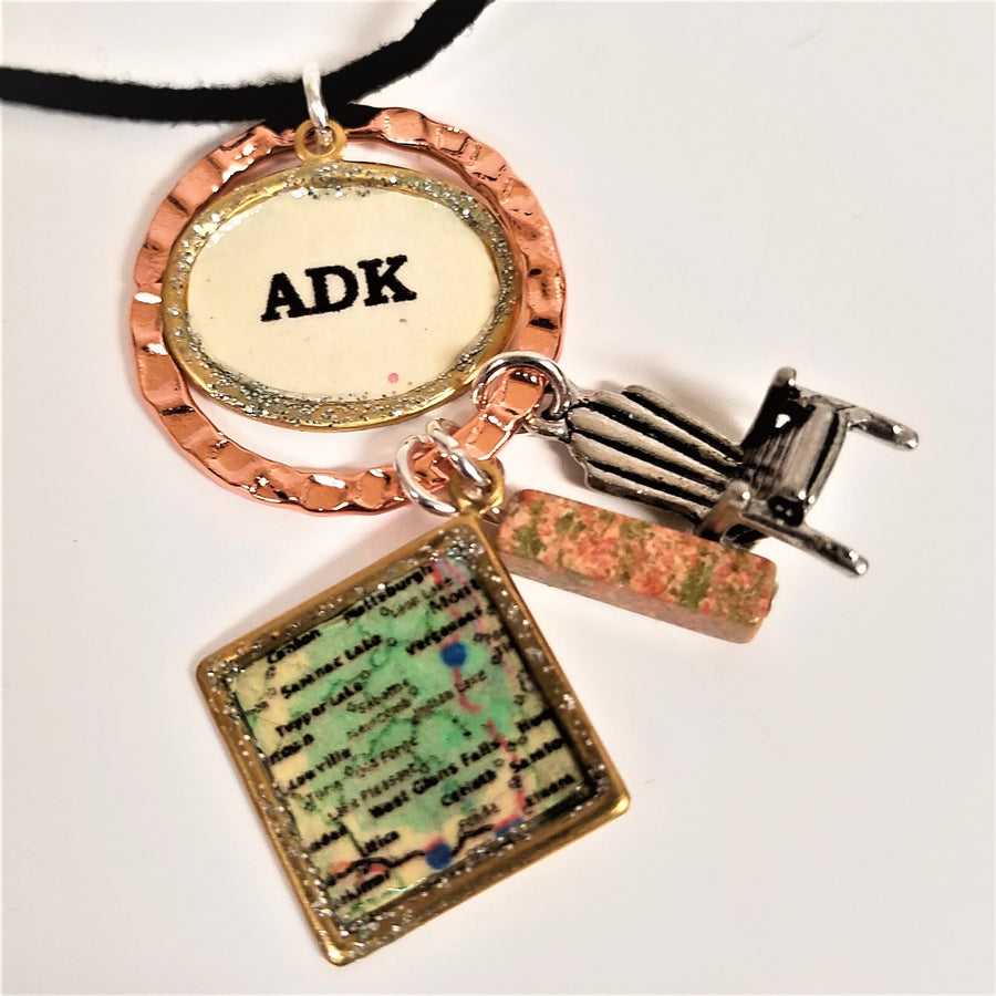 Hanging from a partially seen black necklace cord are a copper-colored ring surrounding a gold oval framing a white oval with the black letters ADK printed centered in the oval. Hanging from the copper ring are three charms: a square-framed map of the greater Saranac Lake area, a pink/green speckled rectangular stone cube, a silver Adirondack chair.