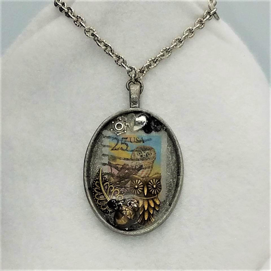 Silver chain with oval pendant featuring an owl-themed collage. Centerpiece is 25-cent canceled owl stamp with gold metal owl perched below. The colors on the stamp are sky blue with yellow surrounding the lower part of the brown-and-white owl.