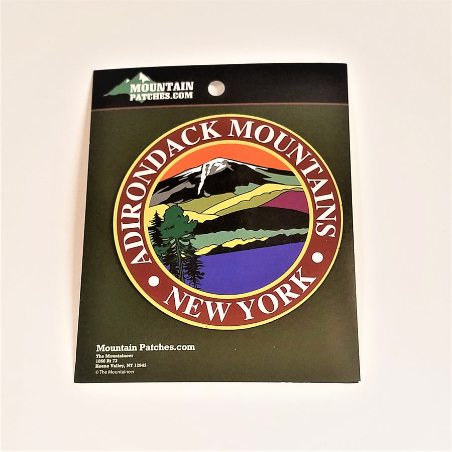 Full view of the Adirondack Mountains magnet on its green packaging. A thin gold circle surrounds the white text: ADIRONDACK MOUNTAINS NEW YORK in the center circle an iconic color line art drawing of the mountains, water and evergreen.