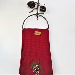 cast iron pine cone towel ring holding a red, pine cone tea towel