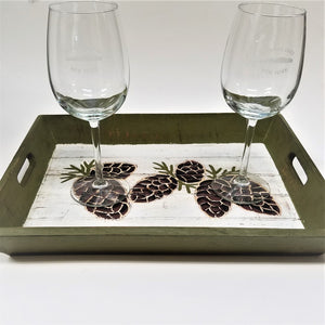 Pine cone tray flat view with two Saranac Lake engraved wine glasses atop.
