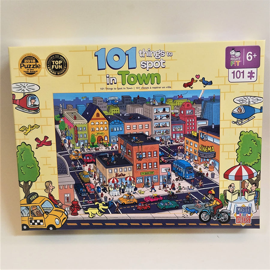Puzzle box cover for 101 things to spot in town with a pale yellow border and colorful buildings in city blocks with blacktop streets filled with colorful cars, buses, bikes and people.