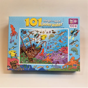 Puzzle box cover for 101 things to spot underwater. Blue border with various sea images.  A thin white border surrounds a brown shipwreck and lots of colorful underwater life, treasure and more.