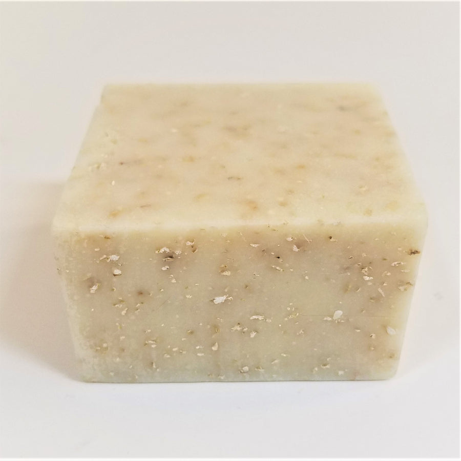 Off-white square soap bar with beige speckles on front side and top of bar.