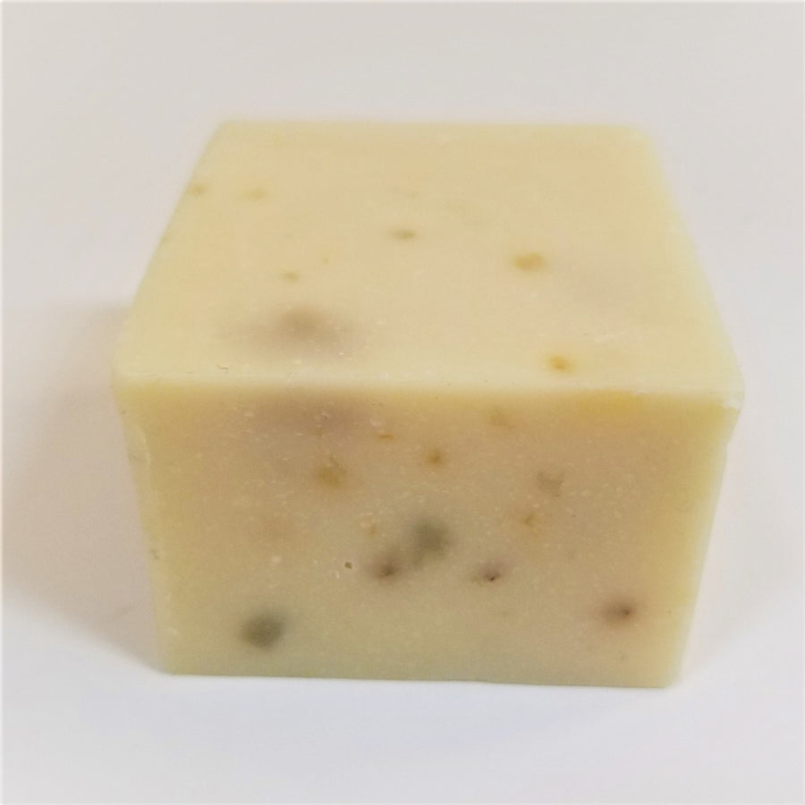 Off-white soap bar with gray specks on front side and gray and pale yellow specks on top.