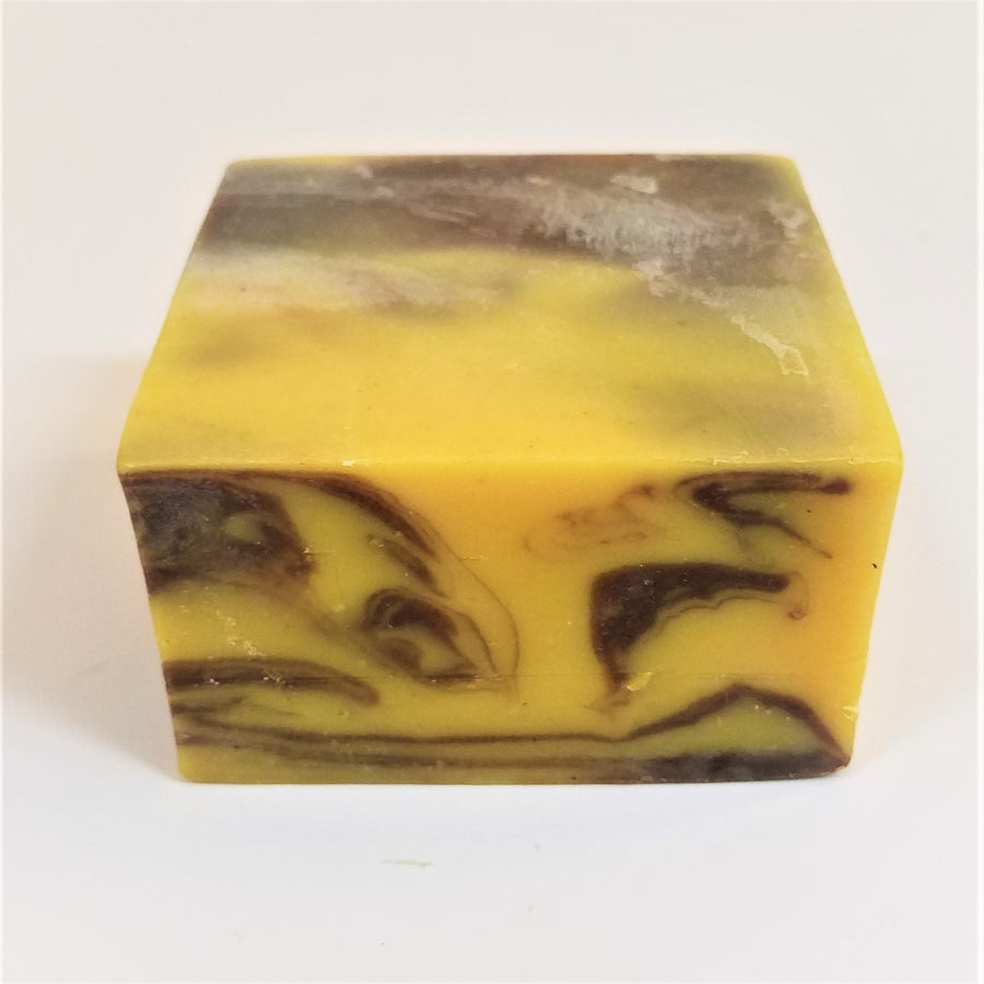 Yellow square soap bar with brown marble front side; top third yellow, back third shades of brown.