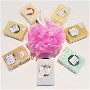 Seven bars of Silky Sudz soap in 7 different scents lying flat surrounding a pink mesh body scrubber.