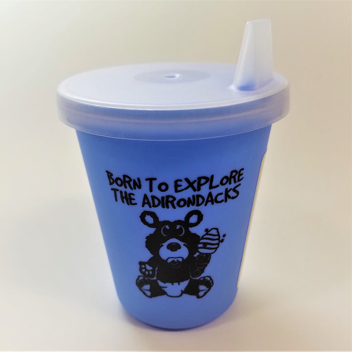Baby blue sippy cup standing upright with clear top attached