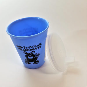 Baby blue sippy cup standing upright with clear spouted top leaning alongside