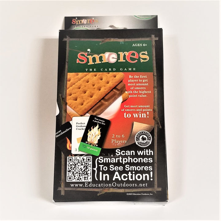 S'Mores card game in boxed packaging. Black box with inside wood-like frame, green rectangular top under type, partial picture of s'mores on red background. Bottom white type with QR code for smartphones.