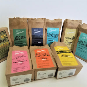 9 bags with labels featuring 9 varieties of SallyeAnder soaps. Beige bags with colorful labels. Six bags standing upright in back; three lying flat in front.