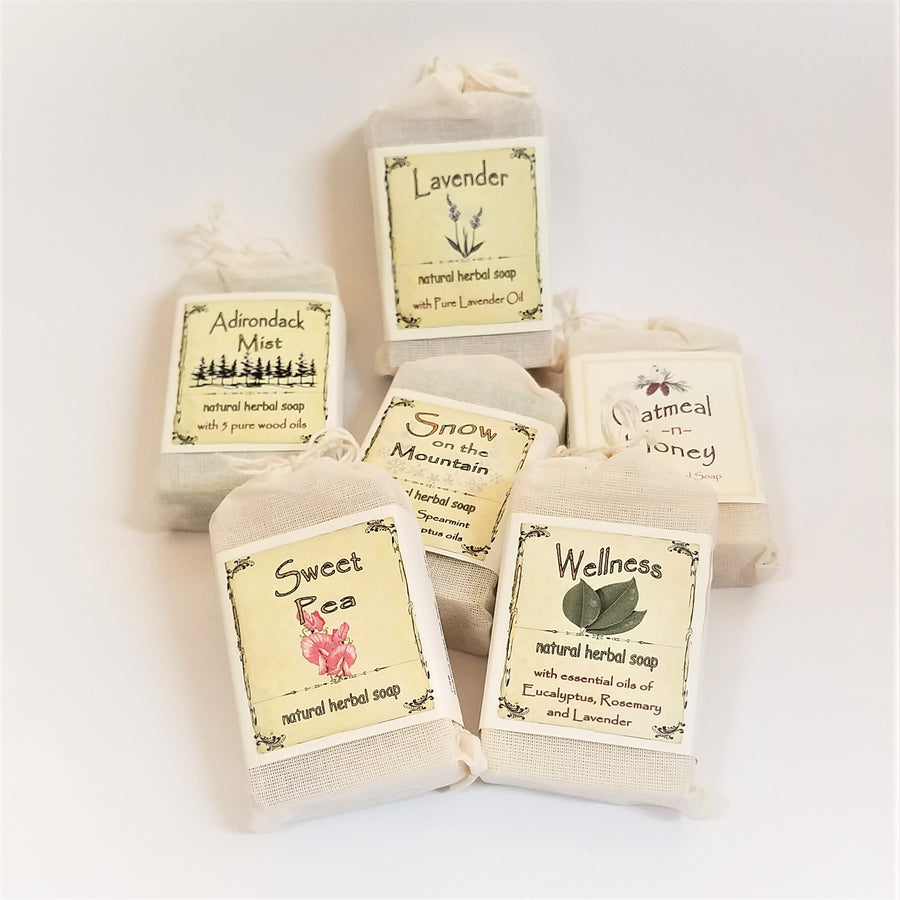 Six packages of bar soap in faux canvas bags with paper labels for each variety of soap