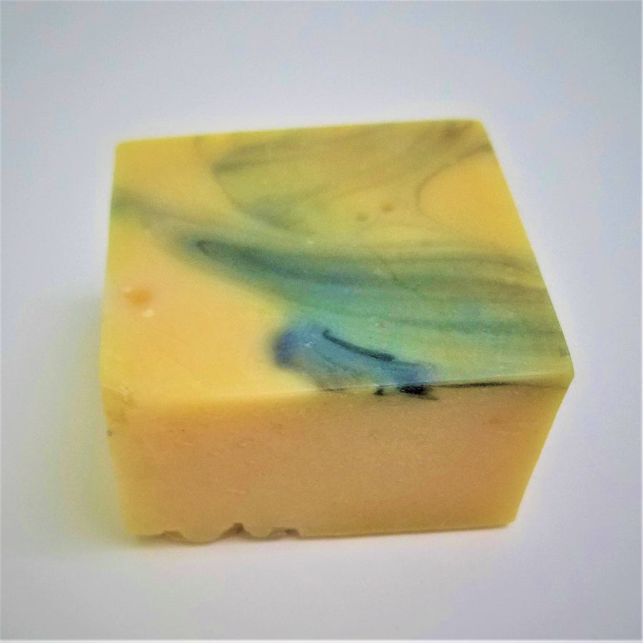 Pale yellow  square soap bar with blue marbled top.
