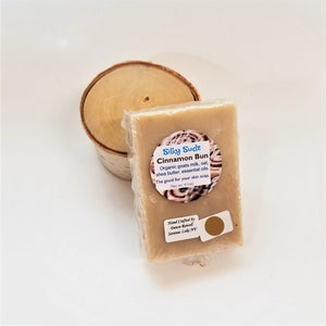 Beige bar of Cinnamon Bun  Silky Sudz soap leaning on a small birch round.