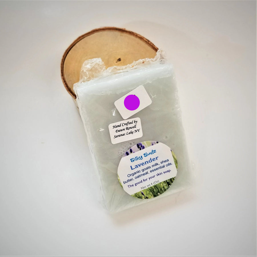 Pale gray bar of Lavender Silky Sudz soap leaning on a small birch round.