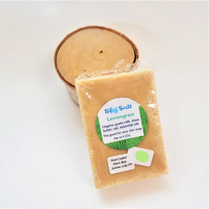 Pale beige bar of Lemongrass Silky Sudz soap leaning on a small birch round.