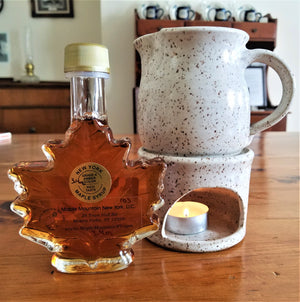 Maple syrup in maple leaf glass bottle with gold top on a wooden table left of a white-speckled mini ceramic pitcher for maple syrup warming sitting atop a matching white-speckled tea candle holder with lit tea candle inside.