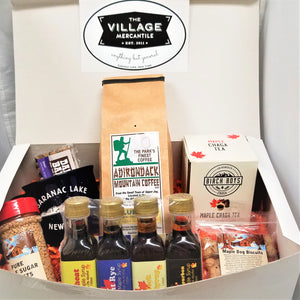White box open to show Village Mercantile logo onto and an assortment of products in the body of the box: red-capped pure maple sugar nuggets, four barrel-aged syrups standing together, plastic package of Maple Dog Biscuits. Behind that a white box of Birch Boys Maple Chaga Tea, next to a beige package of Adirondack Mountain Coffee, next to a black Saranac Lake mug with a Dak Bar sticking out ot it.