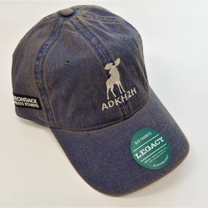 side front view of pre-washed looking blue cap with white moose and white lettering in front and on side. Green label with white text on brim.