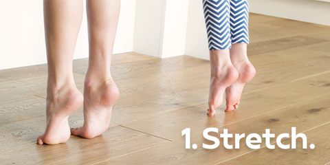 Two sets of feet stretching with toes on ground and heels lifted