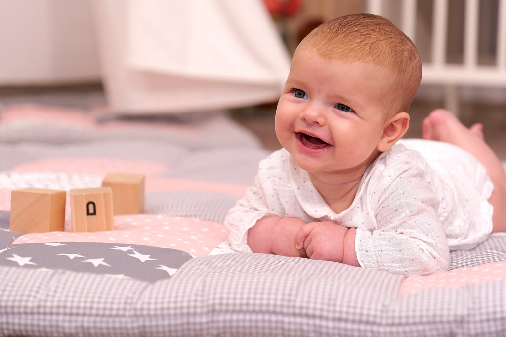laughing baby on play mat in rose pink with stars by ullenboom