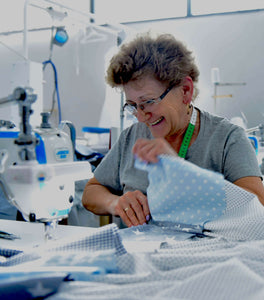 Laughing woman sewing blanket for ullenboom