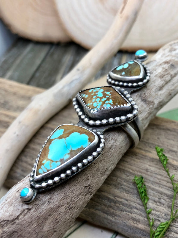 Three perfectly unique turquoise gems from the Nevada Number 8 mine are arranged in row spanning the finger.  This mine was founded in 1925 and produced some of the most sought-after turquoise from the United States. It is no longer mined for turquoise and thus the gems are rare and hard to find. In this ring, the eye jumps from one blue pool to the next.  The turquoise is accented with sterling silver balls and tiny blue drops at each end.  Fits a size 8 finger and adds teal flair to