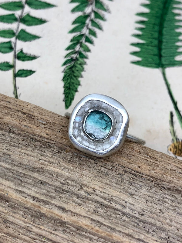Look for something calming to banish fears and phobias.  The clarity and promise of a rainbow after a clearing storm are captured in this stunning light-filled composition. A single bi-color tourmaline centered in a halo of rainbow moonstones recalls the fleeting beauty and serenity of refracted sunlight in the rain. Wear this lovely size 8 ring in any weather for a fresh and striking statement.  • Bi-color rosecut tourmaline  • Rainbow moonstones  • Fine and sterling silver  • Size 8