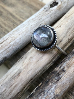A labradorite with purple flash is bezel set and surrounded by sterling roping.  Finished on a size 7 knife edge shank and antiqued to enhance the fine details.  Product Details:  • Labradorite • Solid sterling silver • Size 7